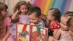 Boy holding alphabet, girls sit around. Stock Footage