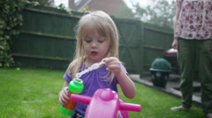 4K Toddler twins playing in the garden with older sister & their mother Stock Footage