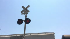 Railroad crossing with train stopped and light flashing Stock Footage