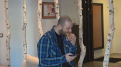 Stock Video Footage of Portrait of young business man inside eating chocolate croissant, sliding phone