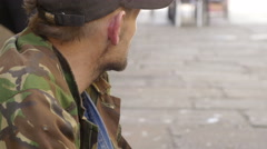 Closeup portrait of a begging young man in the street Stock Footage