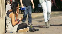female beggar street artist playing on the sidewalk - stock footage