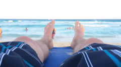 At the beach view of person relaxing on chair Stock Footage