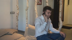Happy business man inside apartment, talking on smartphone, smiling rich people - stock footage