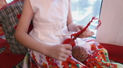 Girl pulls a red yarn on a wooden stick. Stock Footage