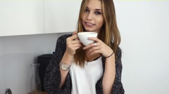 Beautiful young girl drinking coffe in the kitchen. Indoor pfoto - stock footage