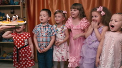 Young children blow out the candles on the cake and happy. - stock footage