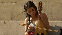 young female street artist playing string  - stock footage