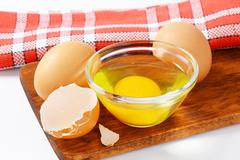 Fresh egg white and yolk in glass bowl, two whole eggs and eggshell - stock photo
