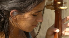 closeup footage of a young female street artist playing music  - stock footage