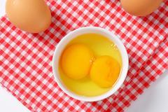 Fresh egg whites and yolks in white bowl - stock photo