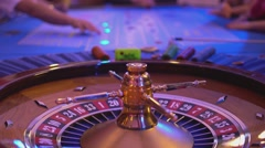 Roulette table in a casino - groupier sorts gambling chips during play - stock footage