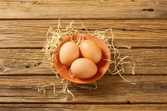 Three brown eggs on terracotta plate on wooden background - stock photo