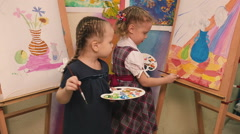 Two little girls standing at the easel and paint. - stock footage