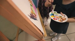 Two little girls draw paints on canvas. Stock Footage