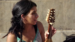 young bulgarian woman playing a string instrument in the street: asking charity - stock footage