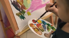 Girl draws on the easel with a brush . Stock Footage