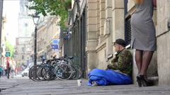 Young outcast homeless begging in the street among the passers Stock Footage