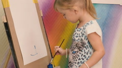Little girl draws a blue paint on paper. Stock Footage