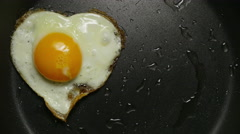 Couple eggs in frying pan. Form of heart. Stock Footage