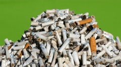 Cigarette butts on green background Stock Footage
