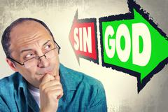Portrait of adult man faced with choice between SIN and GOD Stock Photos
