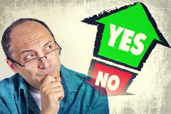Adult man thinking what to choose between YES and NO - stock photo