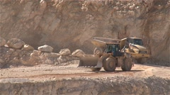 Heavy building bulldozer and  dump truck passing on a road in a quarry Stock Footage