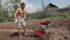 Athlete man is working in the field with ripper cultivator Stock Footage