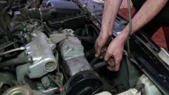 Oil Change mechanic at the service station connects the spark plug wires Stock Footage