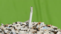 Cigarette butts on green background, time lapse Stock Footage