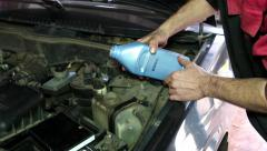 Oil Change mechanic Refill the engine coolant in the reservoir at the service - stock footage