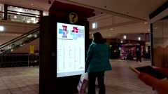 Woman checking store position in front of directory sign inside shopping mall Stock Footage