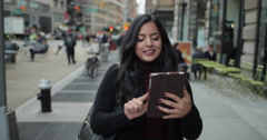 Young Indian woman in city walking using tablet computer - stock footage