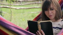 Girl in hammock reading a book - medium shot - stock footage