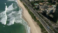 Stock Video Footage of Overhead Aerial shot of Sandy Beach with Waves and City Buildings