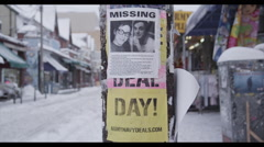 CU missing person sign on pole on winter day Stock Footage