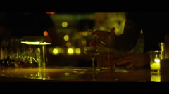 Bartender pours drink in yellow moody lit bar Stock Footage