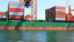 Containers stacked on the deck of green cargo ship Stock Footage