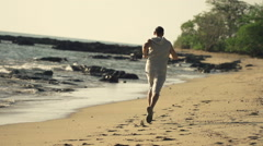 Young man jogging on beach, super slow motion 240fps - stock footage