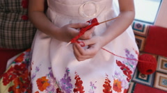 Girl doing crafts of red yarn and wooden sticks. Stock Footage