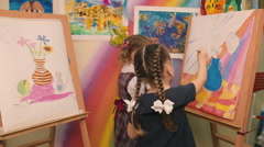 Two little girls sit and paint brushes on canvas. Stock Footage