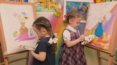 Two little girls standing at the easel and paint colors. Stock Footage