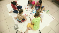 Little girl paint colors on a large canvas on the floor. Stock Footage