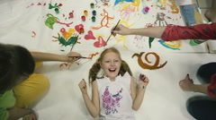On the floor lies a little girl on top of color pictures, the children paint. Stock Footage