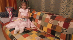 Small needlewoman in a pink dress sitting on a sofa and embroiders. Stock Footage