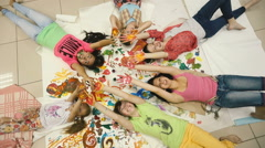Little girls lie on the floor in the picture and waving their hands. Stock Footage