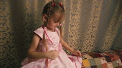 A cute little girl with pigtails in a pink dress hangs over the colored ribbons. Stock Footage