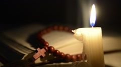 Candle burning against of the Bible and cross Stock Footage