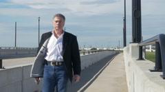 Businessman walks past camera on bridge walkway 4k Stock Footage